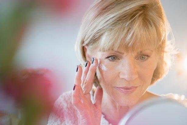 Older-Caucasian-woman-applying-moisturizer-to-face.jpg