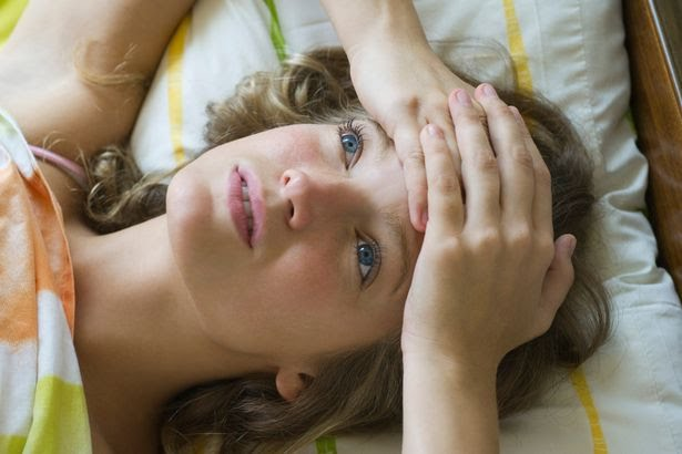 Young-woman-lying-on-bed-with-hands-clasped-on-forehead-looking-up-in-thought.jpg